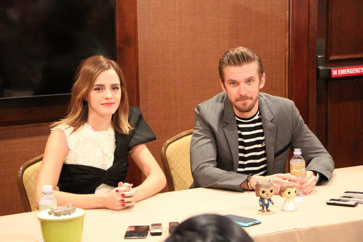 Emma Watson, Dan Stevens sitting at a table