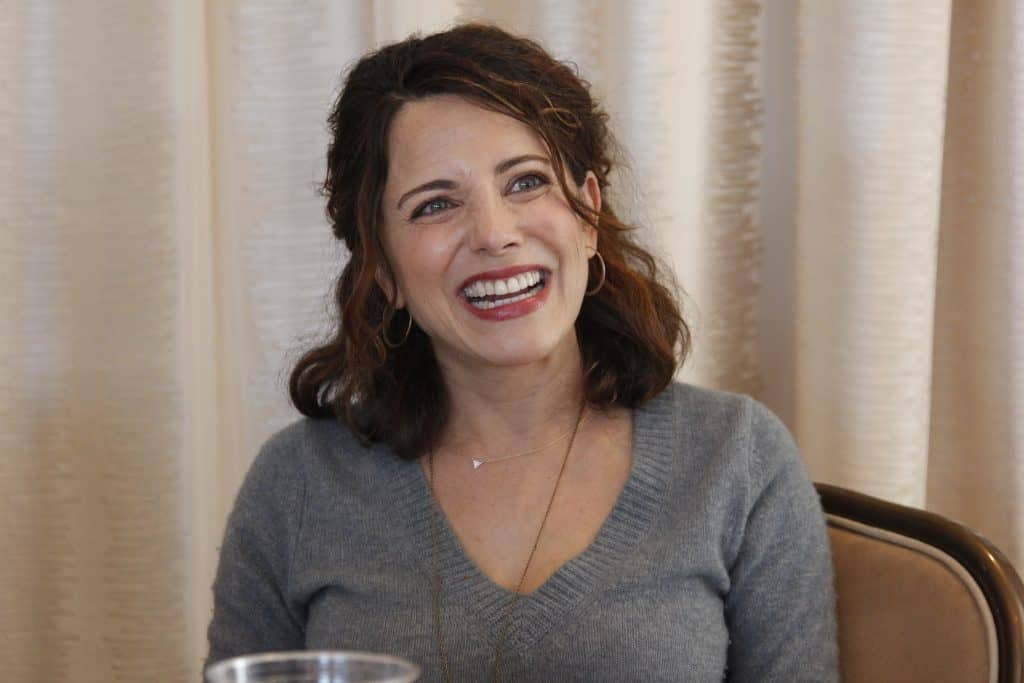 Alanna Ubach sitting at a table in front of a curtain