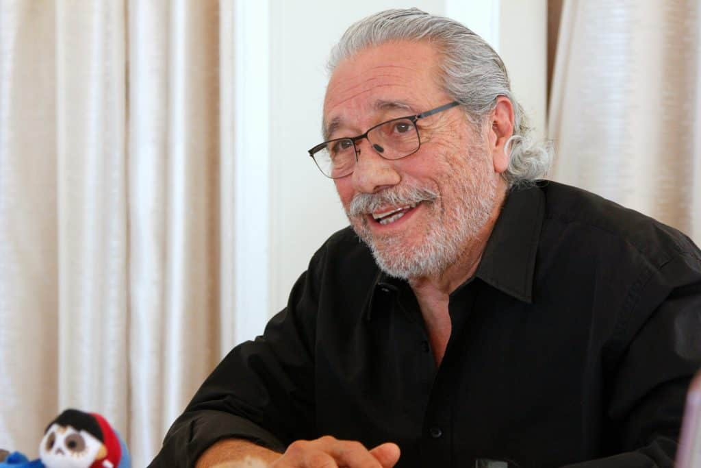 Edward James Olmos sitting in front of a curtain