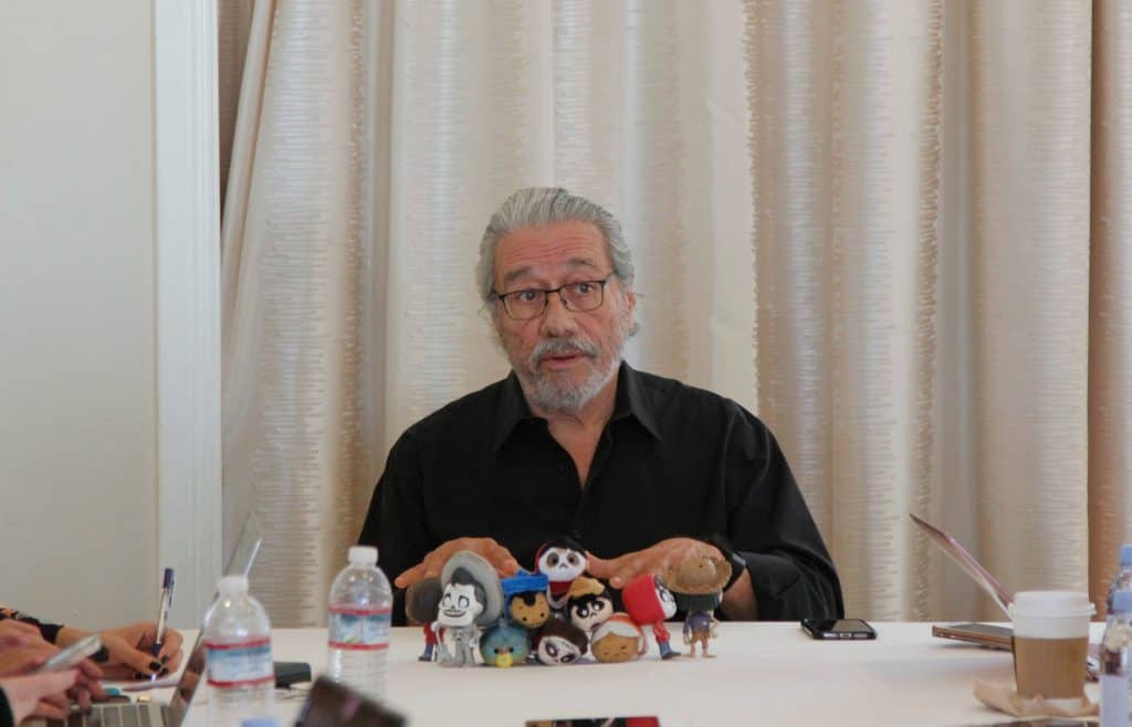 Edward James Olmos sitting at a table in front of a curtain
