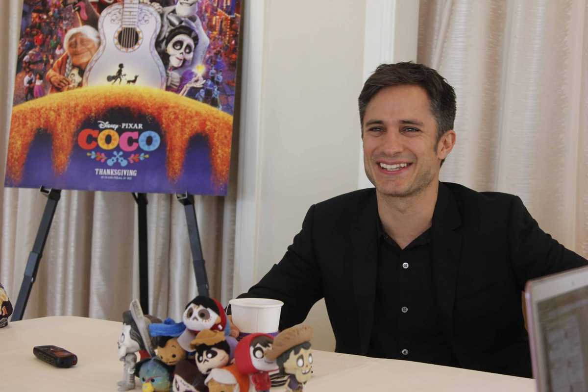 Gael Garcia Bernal sitting at a table in front of a laptop computer