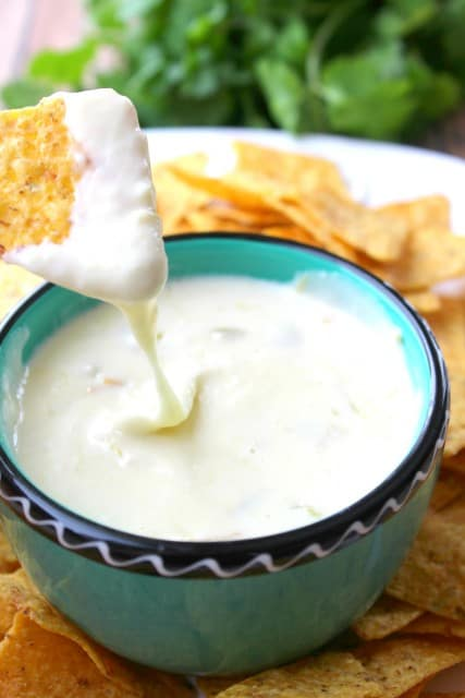 A bowl of food on a plate, with Cheese and Queso blanco