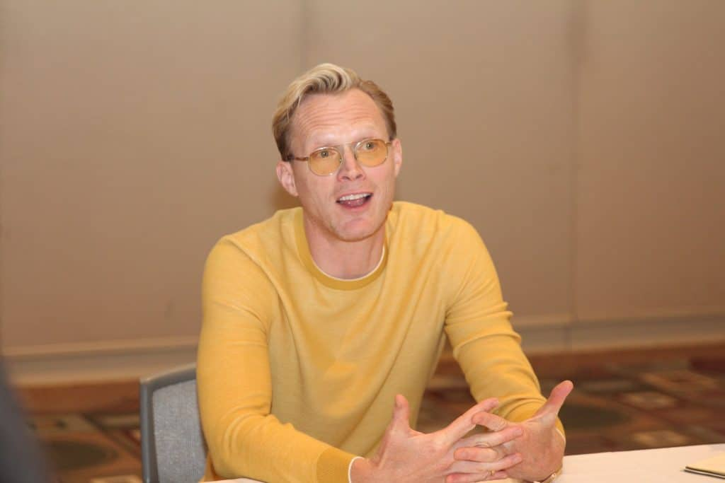 Paul Bettany sitting on a table