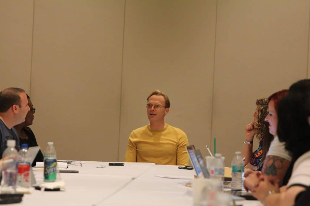 Paul Bettany et al. sitting at a table