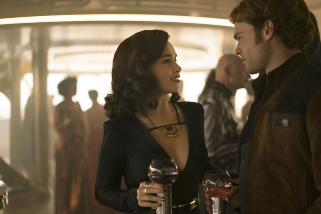 A man and a woman standing next to a glass of wine, with Star Wars