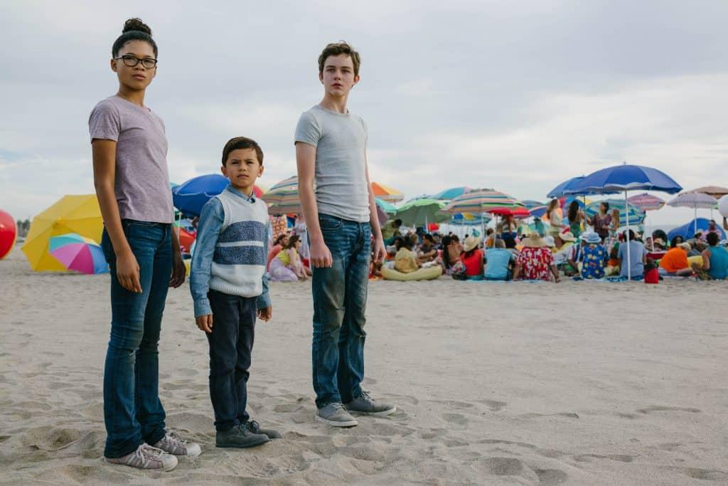 Storm Reid, Levi Miller standing on top of a sandy beach