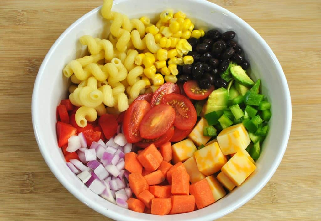 A bowl of fruit on a plate, with Salad and Pasta