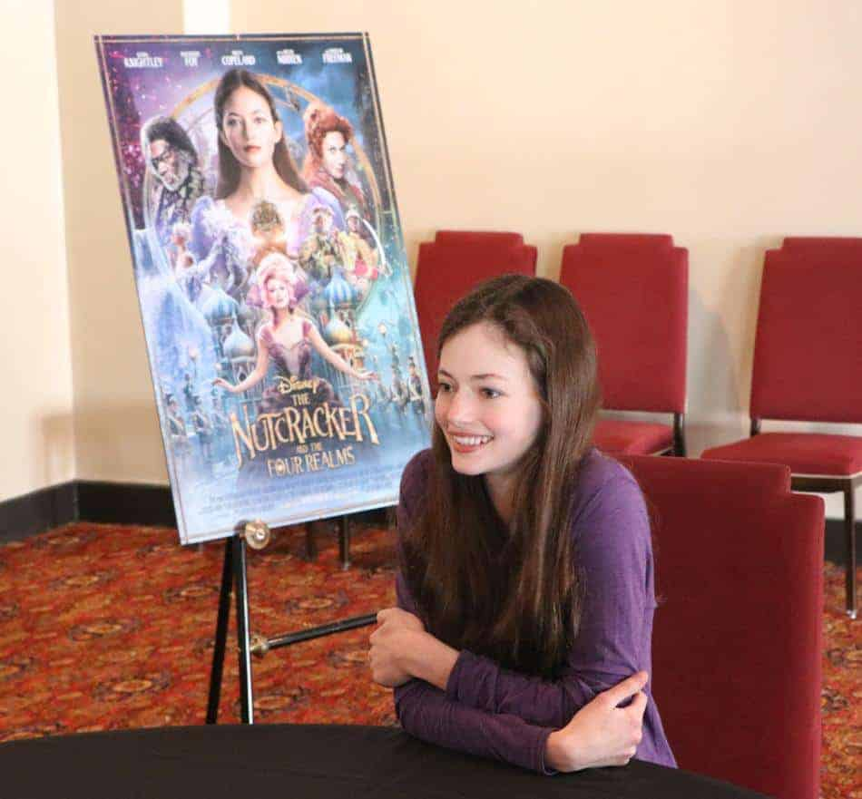 Mackenzie Foy sitting at a table using a laptop