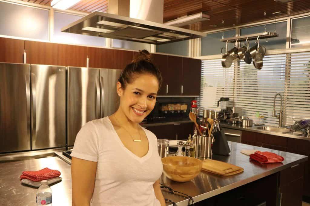 Jaina Lee Ortiz standing in a kitchen preparing food, with Station 19 and Boris Kodjoe