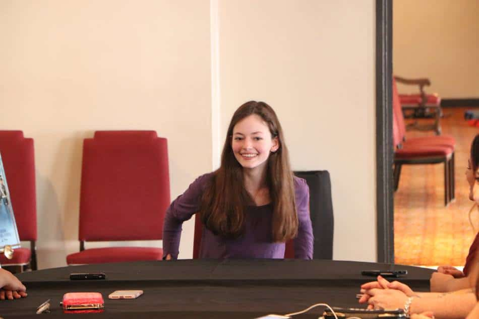 Mackenzie Foy sitting at a table