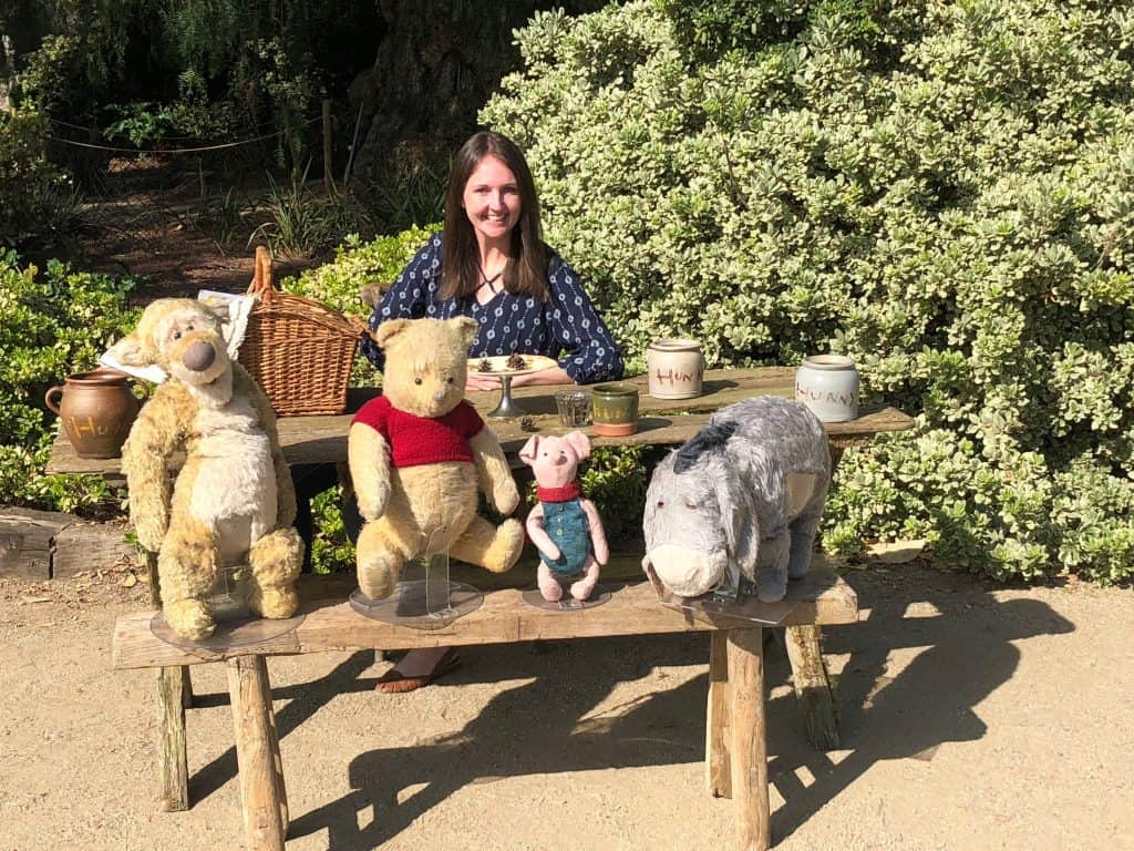 A person sitting on a bench next to a stuffed animal