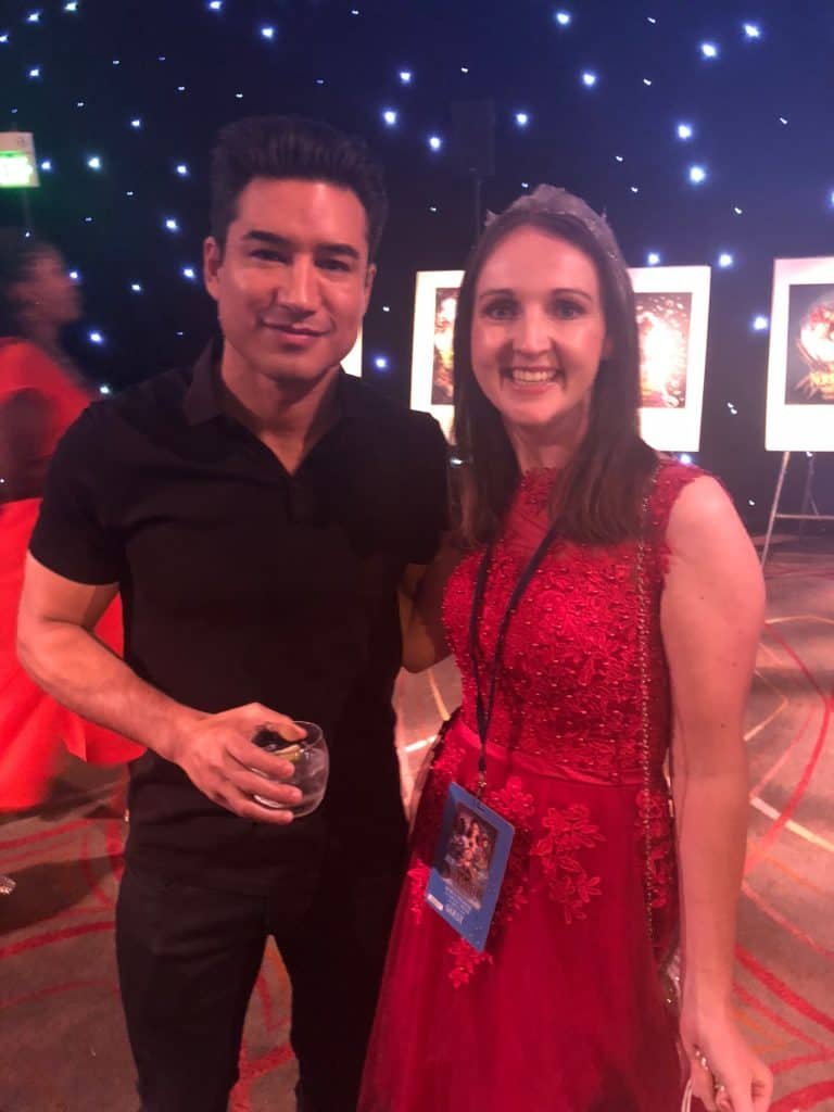A person standing in front of Mario Lopez et al. posing for the camera