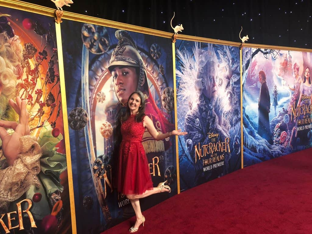 A person standing in front of a red carpet wall