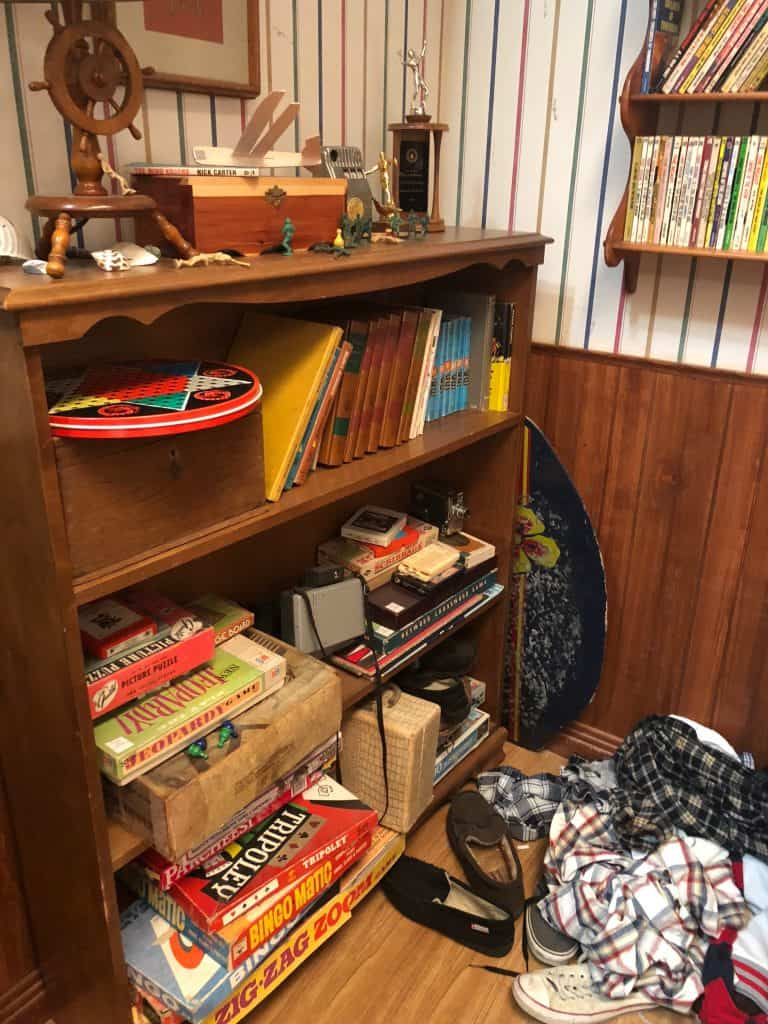 A desk with a book shelf filled with books
