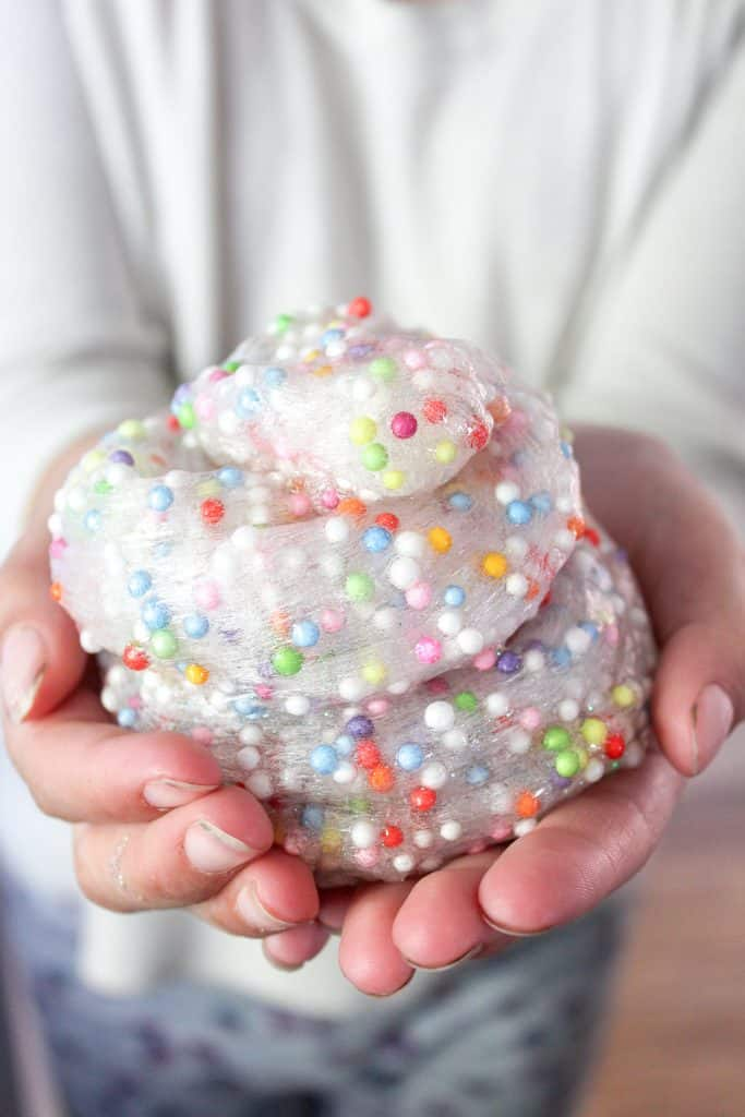 A close up image of colorful slime in hands