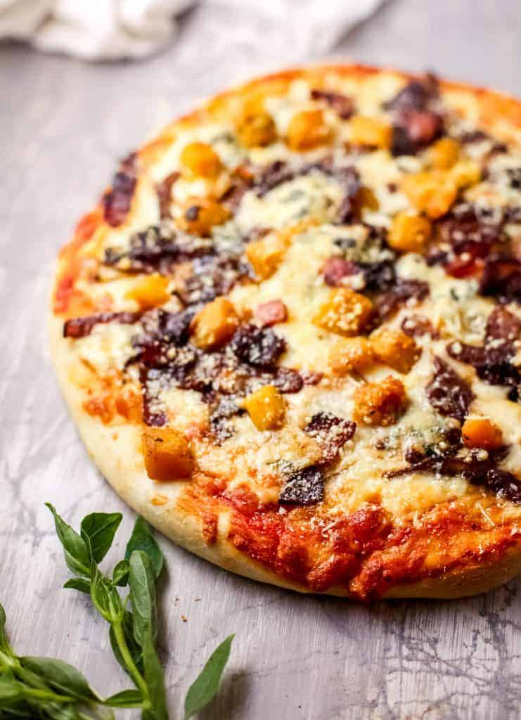 A pizza sitting on top of a wooden cutting board, with Cheese and Harvest